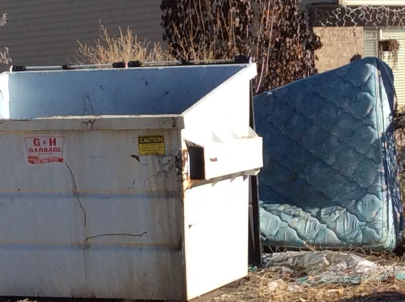 Mattress Sitting Behind a Dumpster